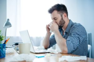 man suffering from a sinus infection at work